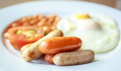 English breakfast with sausages, fried eggs, tomato, and bean