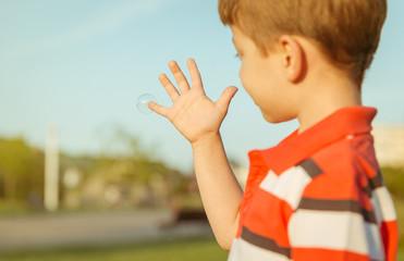 Cute boy looking soap bubble in his open hand
