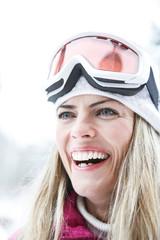 Lachende Frau im Winter mit Skibrille