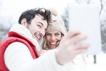 Paar im Winterurlaub macht Fotos mit Tablet Computer