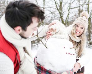 Lachendes Paar baut Schneemann im Winter