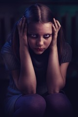 Depressed teen girl sits and cries