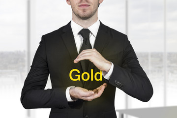 businessman protecting gold with hands