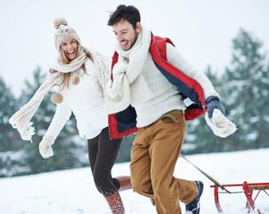 Paar läuft mit Schlitten durch Schnee