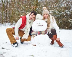 Glückliches Paar mit Schneemann im Winter