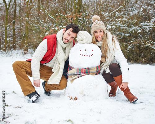 canvas print picture Glückliches Paar mit Schneemann im Winter