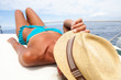 Attractive girl sunbathing on a yacht holding her hat - 69134054