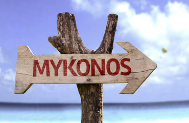 Mykonos wooden sign with a beach on background