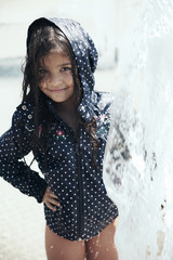 Portrait of a beautiful little girl playing in the fountain