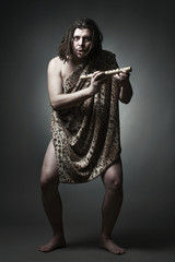Primitive wild man learn to play music with flute.