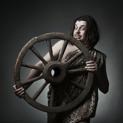 Caveman wearing leopard skin hold old wooden wheel.