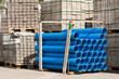 Ein Stapel blauer Rohre vor Paletten mit Pflastersteinen