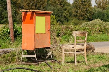 Ein alter Stuhl aus Holz steht neben einem Baustromverteiler