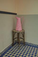 pot à eau rose dans un coin sur tabouret de bois
