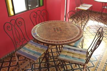table ronde en céramique avec chaises en fer forgé