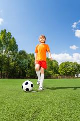 Happy boy kicking football with his leg