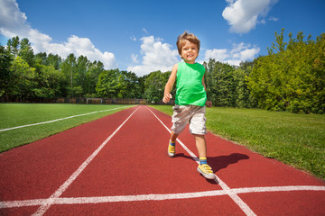 Cute small boy runs slowly on the marathon road