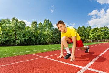 Boy in ready position on one bend knee to run