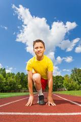 Smiling boy in ready position to run marathon