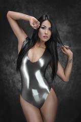 Sexy brunette woman in latex swimsuit