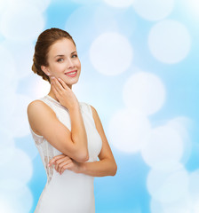 smiling woman in white dress wearing diamond ring