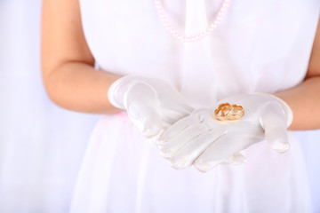 Bride in white dress and gloves holding wedding rings, close-up
