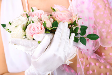 Beautiful bride in white gloves holding wedding bouquet,