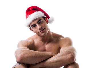 Attractive young muscle man sitting in Santa Claus's red hat
