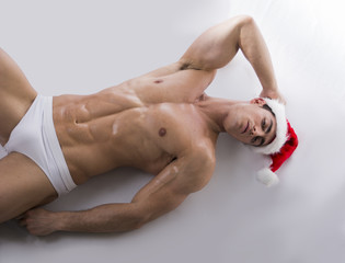 Young muscle man on the floor in Santa Claus's red hat