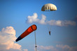 Постер, плакат: single parachute jumper against blue sky background