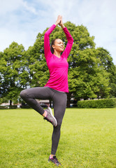 smiling african american woman exercising outdoors