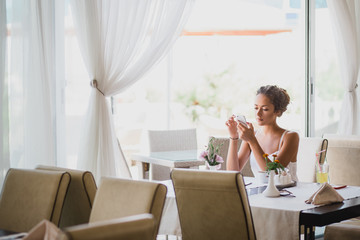 Young woman sitting in a cafe using her phone