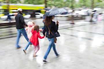 Familie geht bei Regen in der Stadt