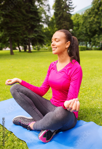 canvas print picture smiling woman meditating sitting on mat outdoors