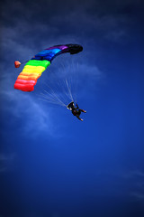 single parachute jumper against blue sky background