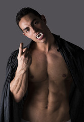 Naked muscular fit young man posing as vampire or Dracula