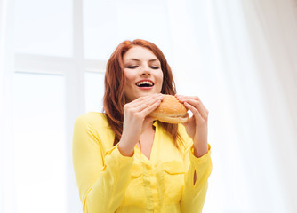 smiling young woman eating hamburger at home