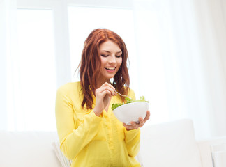 smiling young woman eating green salad at home
