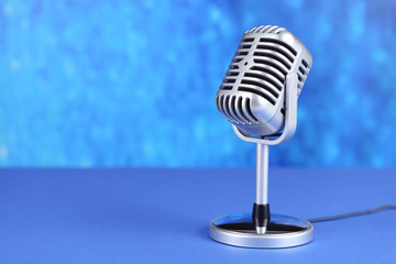 Vintage microphone on table on blue background