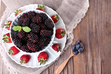 Bowl of blackberries and plate of strawberries
