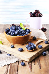 Wooden bowl of blueberries and metal mug of blackberries