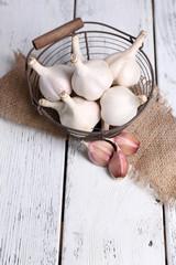 Fresh garlic in basket, on wooden background