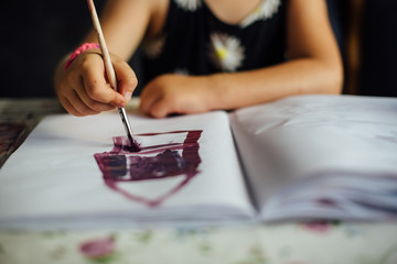 Little preschool girl painting at home