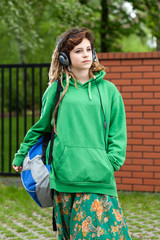 Teenage girl with backpack listening to music