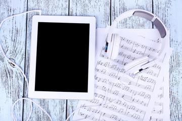 Tablet, printed music and earphones on wooden background
