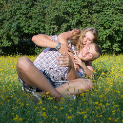Portrait of a happy couple embracing and playing at the lawn.