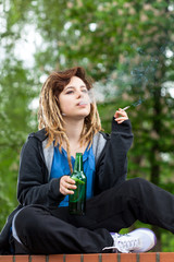 Teenage girl drinking beer and smoking cigarette