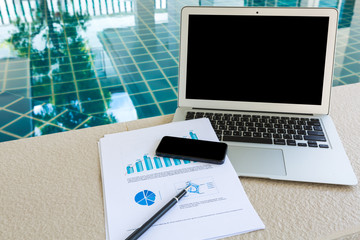 Laptop, tablet , smartphone  with financial documents at swimmin