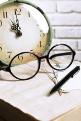 Retro clock and glasses on table in room