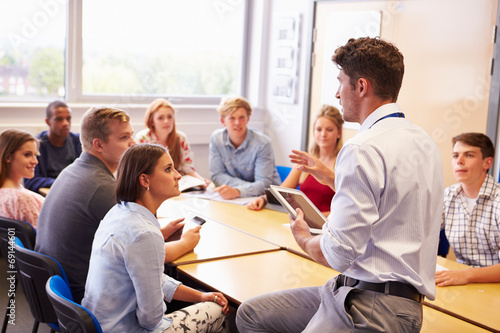 Teacher With College Students Giving Lesson In Classroom poster